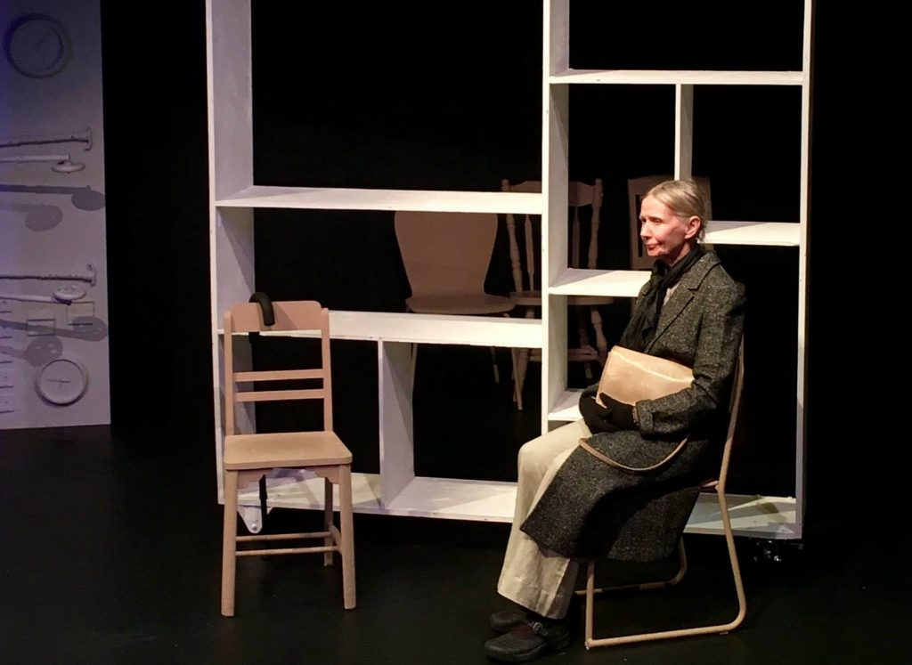 """An older adult sitting on a chair holding their purse during a performance of """"The Golden Cage"""". They stare off into the distance."""