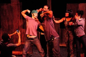 A group of young adults performing on-stage. Two people stand with their fists raised up, poised to punch each other. Another person is seated and taking a photo of them. Three other people are looking at the fight.
