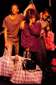 Three people performing on-stage. One person is holding a purse and a large bag in one hand and touching her other hand to their cheek. Two people stand behind them, one of which also holds a large bag.