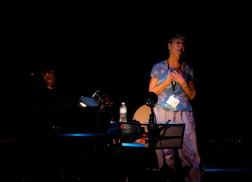 A person performing on a stage, holding their hands to their chest. In front of them is a table with a waterbottle and other items on top of it. She is illuminated the most brightly in the photo.an see