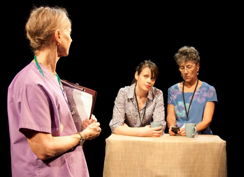Three people on stage performing. Two people are seated at a beige table holding coffee mugs. The third person is dressed as a nurse and is standing in front of the table holding a clipboard.