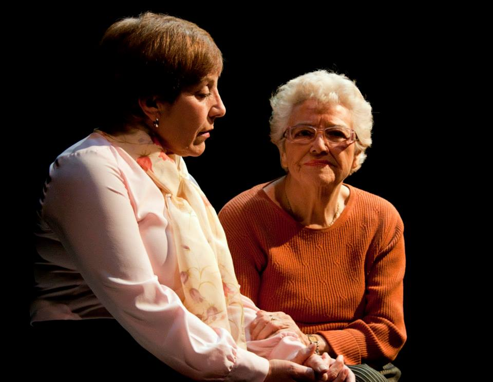 Two people performing on-stage. One is an older adult who is holding the other person's forearm. They are both seated.