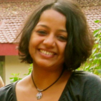 Swetha Ranganathan standing in front of a tree and a building.