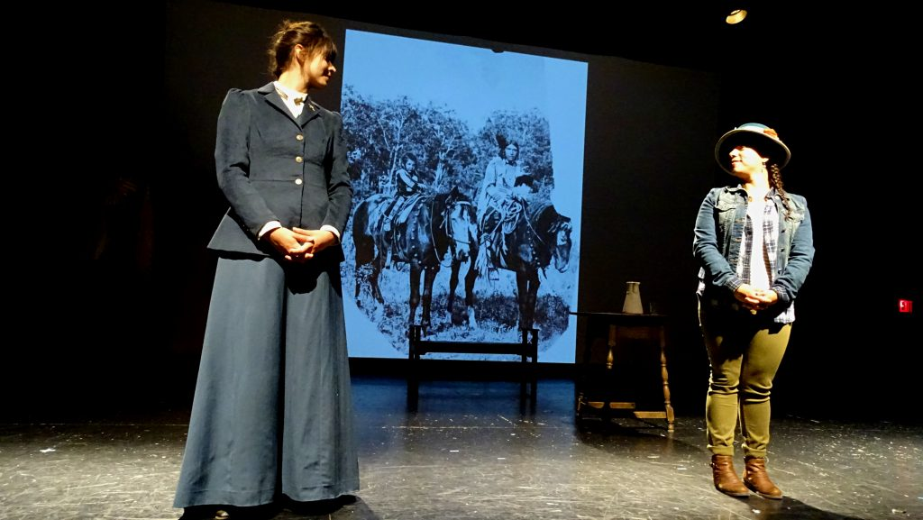 Two actors are performing on a stage, staring at each other. One is dressed in a navy jacket and long skirt, while the other is in modern dress. There is a screen projecting an image of two people on horseback in the background.