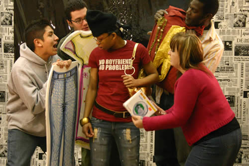 One person stands surrounded by four people who hold up clothing, images of clothing, and a book.