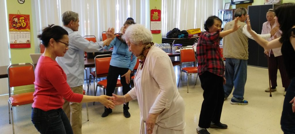 A group of older adults divided into partners, mirroring each others' movements.