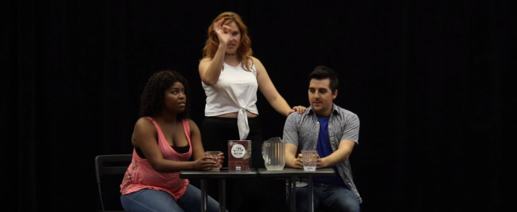 """Three actors in a scene from a post-secondary Mixed Company production. Two people sit at a table while a third person stands between them and has one of their hands up in an """"ok"""" gesture."""