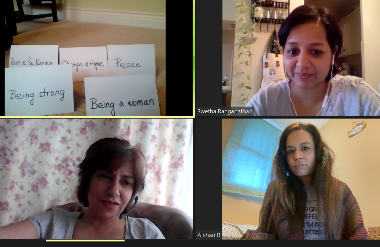 Three women in a Zoom meeting, looking forward. In the top left square there are papers with phrases written on them that relate to female experiences.