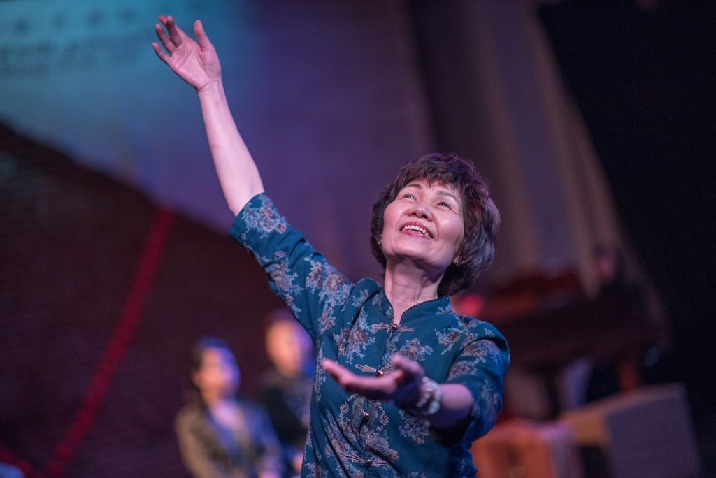 "An older adult smiling with her left arm raised up and her right arm beckoning forward, in a performance of ""Spring Moon""."