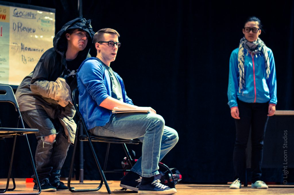 Three actors performing in one of MCT's school productions. One person has their hood up and they are standing behind another person who is seated on a chair. The third person is off to the side looking at the others.