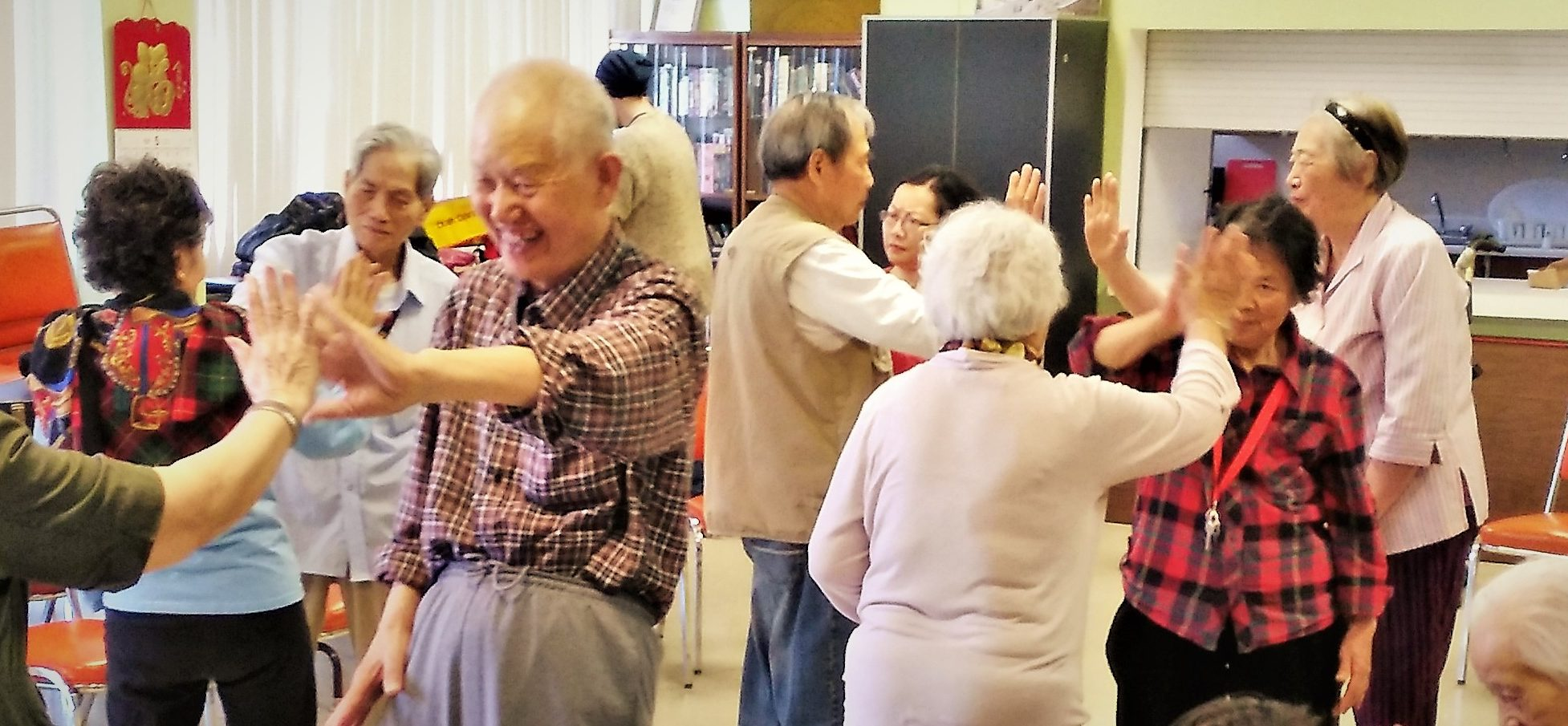 A group of older adults engaged in a mirroring theatre exercise.